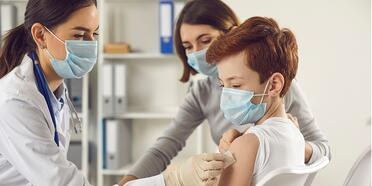 doctor-in-face-mask-giving-vaccine-to-little-boy-who-came-to-the-picture-id1298103455